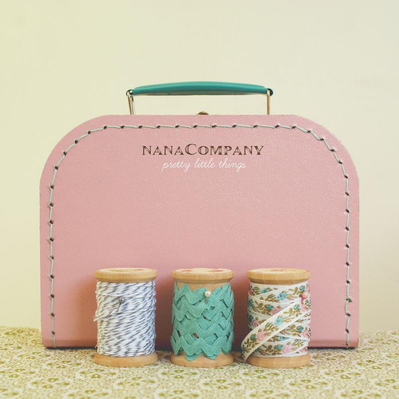 pink suitcase and wooden spools